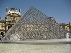 The entrance to the Louvre, surrounding by many fountains.